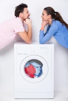O casal coloca os cotovelos na máquina e olha um para o outro.