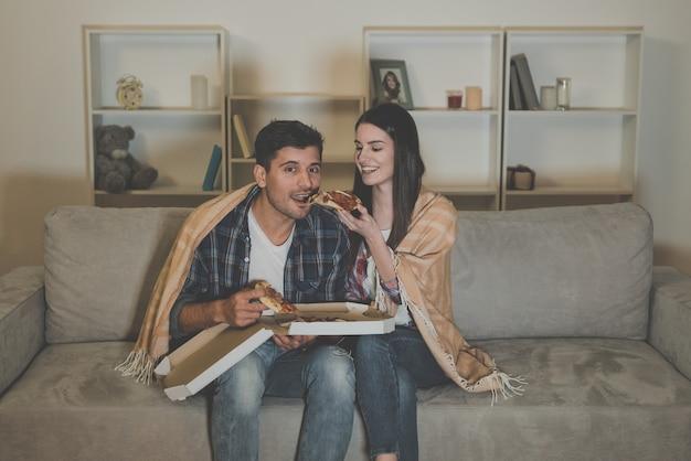 O casal comendo pizza e vendo um filme no sofá