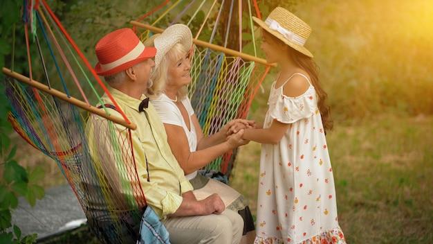 O casal de idosos está sentado na rede no jardim