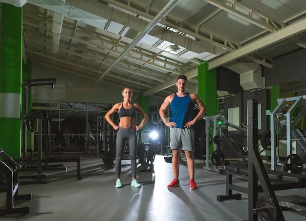 O casal do esporte em pé na academia moderna no fundo claro Foto Premium