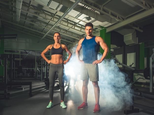 O casal do esporte fica parado na academia, no fundo da fumaça