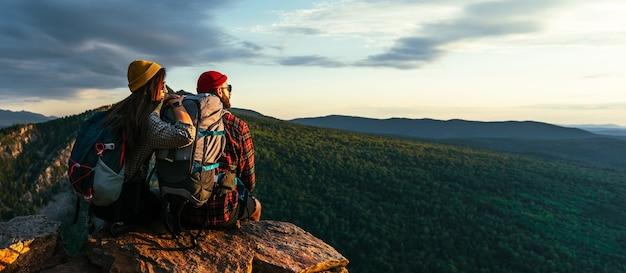 O casal encontra o pôr do sol nas montanhas. dois viajantes estão sentados na beira de um penhasco admirando a bela vista panorâmica. viajantes com mochilas ao pôr do sol nas montanhas. panorama
