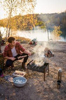 O casal está descansando na natureza. homem preparando churrasco na natureza
