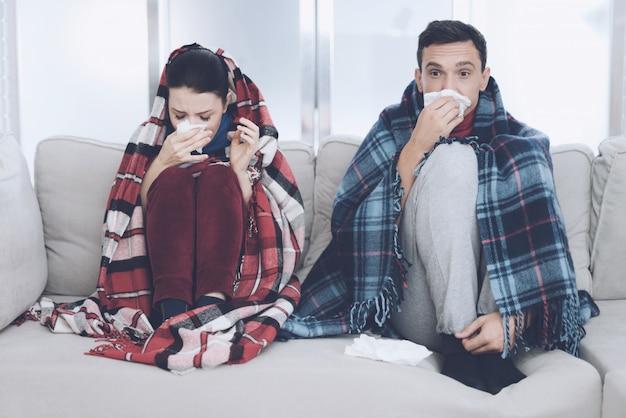 O casal está sentado no sofá envolto em cobertores.