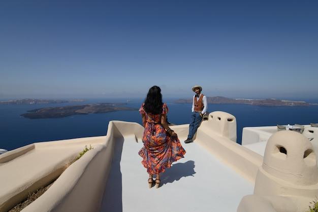 O casal está sentado no telhado em santorini, abraçando e rindo