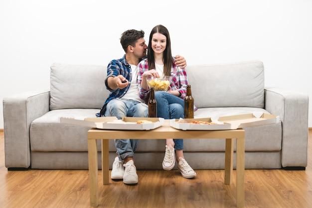 O casal feliz assistindo tv com uma pizza e uma cerveja no fundo branco