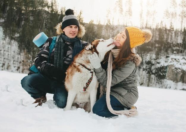 O casal feliz com cão haski no parque natural da floresta na estação fria