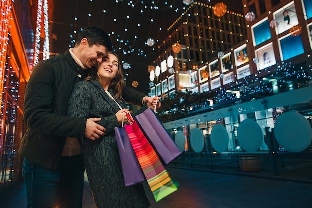 O casal feliz com sacolas de compras curtindo a noite na cidade