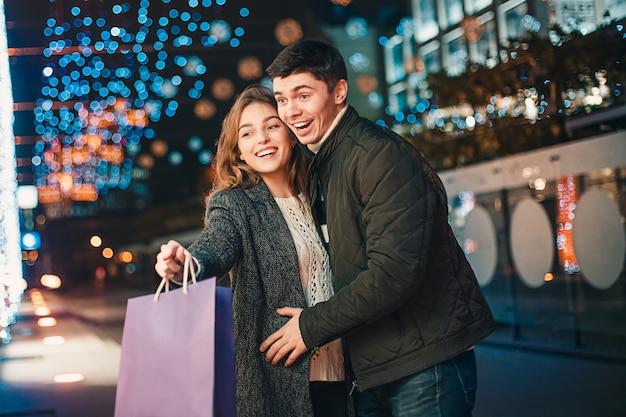 O casal feliz com sacos de compras, aproveitando a noite na cidade