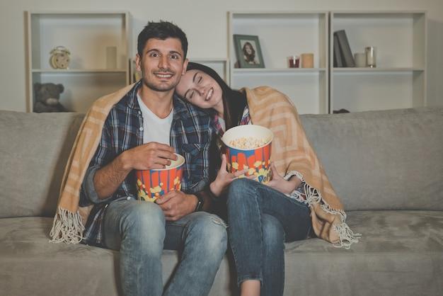 O casal feliz comendo pipoca e assistindo filme no sofá