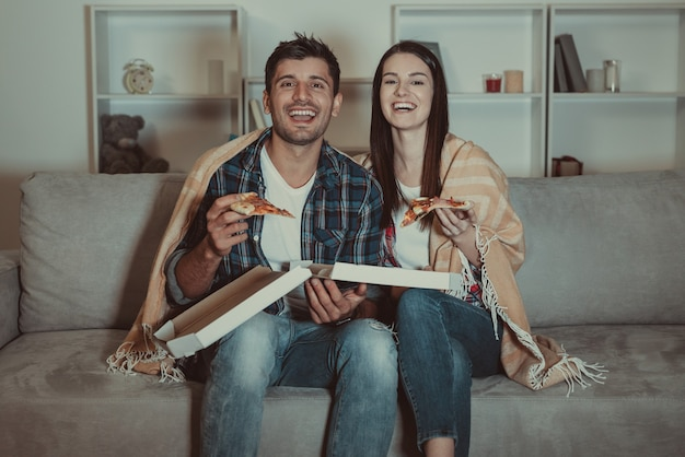 O casal feliz comendo pizza e assistindo a um filme no sofá