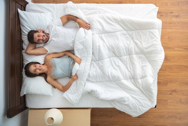 O casal feliz deitado na cama. vista de cima