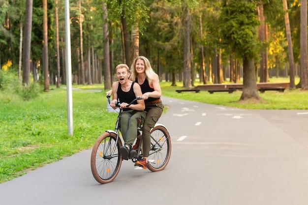 O casal feliz em bicicletas no parque