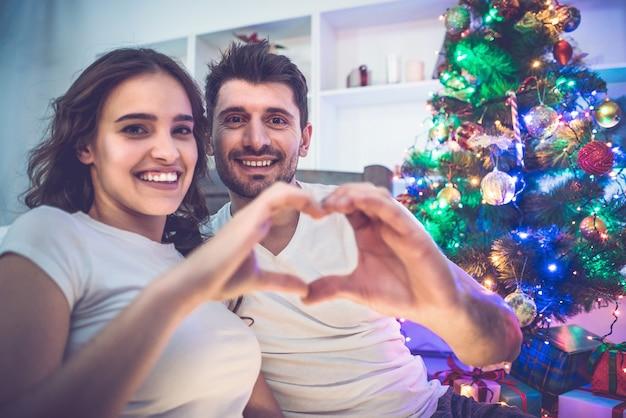 O casal feliz mostra o símbolo do coração perto da árvore de natal