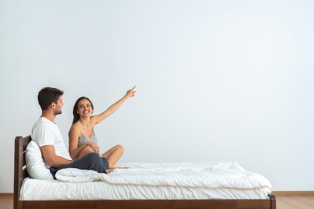 O casal feliz na cama gesticulando no fundo branco