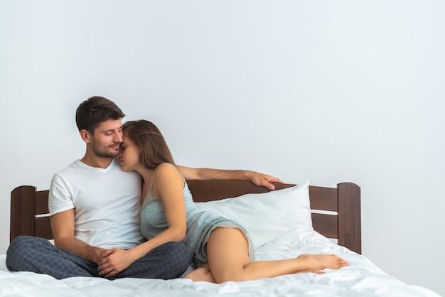 O casal feliz se abraça na cama no fundo branco