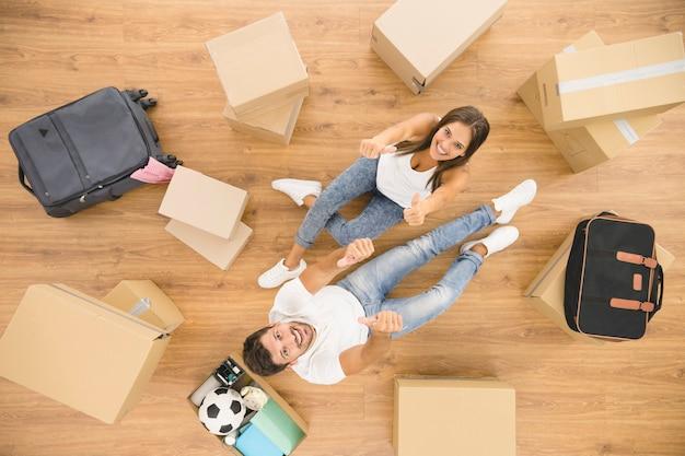 O casal feliz senta-se perto de caixas de papelão e gesticula. vista de cima