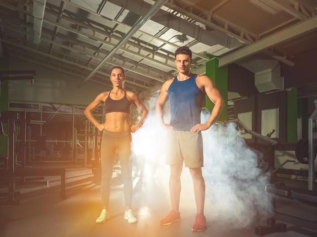 O casal fitness em pé na academia, no fundo da fumaça