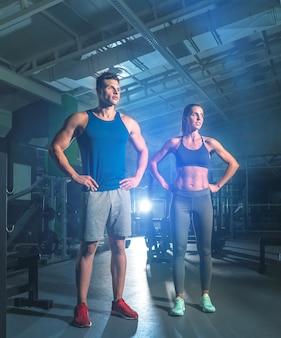 O casal fitness está na academia, no fundo claro