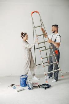 O casal jovem e bonito repara o quarto
