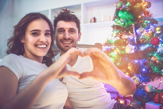O casal mostra um gesto de amor perto da árvore de natal. noite noite
