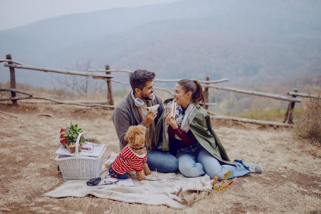 O casal multicultural de sorriso atrativo vestiu o assento ocasional na manta no piquenique e em comer sanduíches. cachorro olhando para eles. estação do outono.