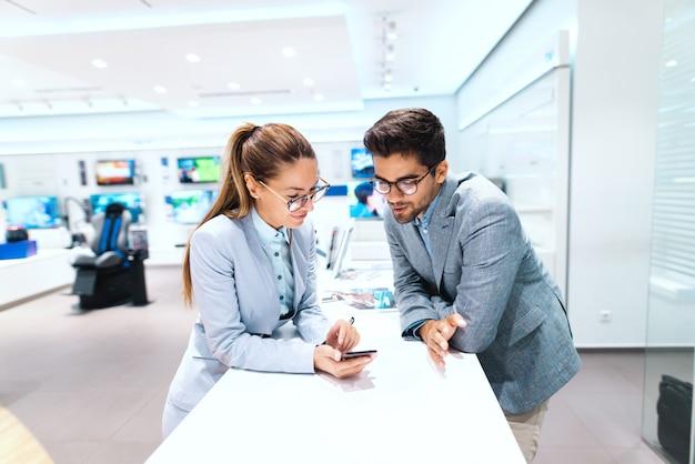 O casal multicultural de sorriso vestiu-se em comprar o telefone esperto novo. mulher experimentando telefone. interior da loja de tecnologia.