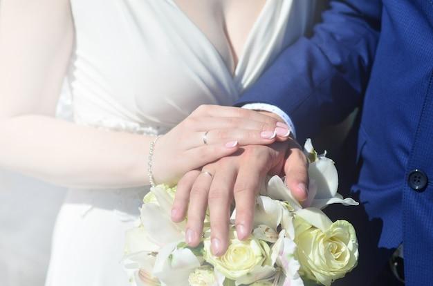 O casal recém-casado está segurando um lindo buquê de casamento