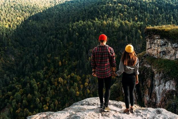 O casal saúda o nascer do sol nas montanhas, vista traseira. um homem e uma mulher nas montanhas. um homem e uma mulher se dão as mãos. um casal apaixonado em uma rocha admira as belas paisagens. copie o espaço
