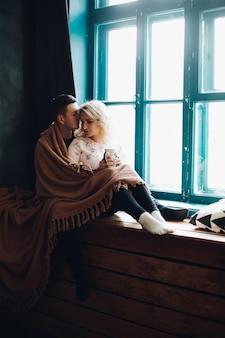 O casal sentado e abraçando ao lado da janela no peitoril da janela.