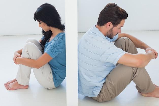 O casal sentado é separado pela parede branca