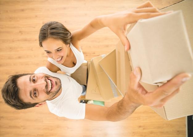 O casal sorridente segura uma caixa de papelão e olha para a câmera. vista de cima