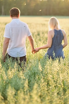 O casal vai em um campo ao pôr do sol de mãos dadas