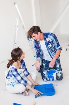 O casal vai pintar a parede, eles estão preparando a cor.