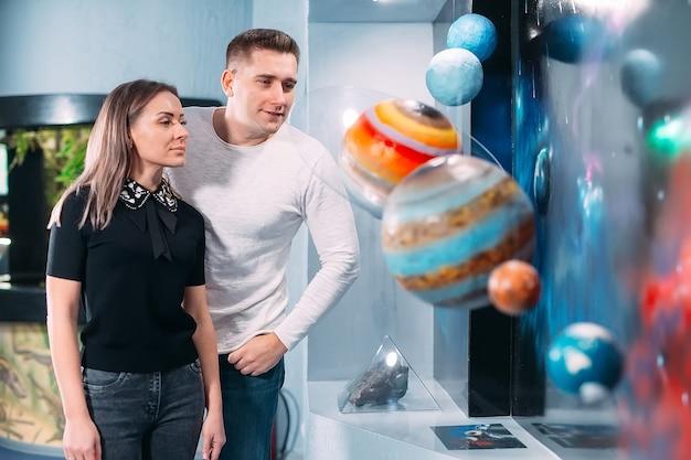O casal vê a exposição dos planetas do sistema solar no museumm.