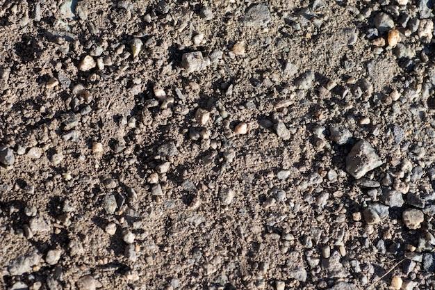 O cascalho grosso, seixos e areia são pretos, multicoloridos. close da textura do fundo