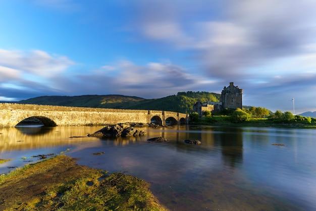 O castelo de eilean donan é uma das atrações mais visitadas e importantes nas montanhas escocesas no pôr do sol com reflexo, escócia