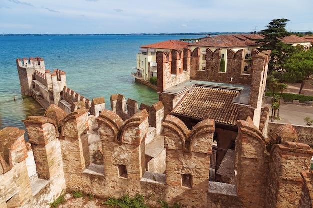 O castelo scaliger é um marco histórico da cidade sirmione, na itália, no lago garda. castelo medieval italiano. as paredes de pedra de uma torre antiga