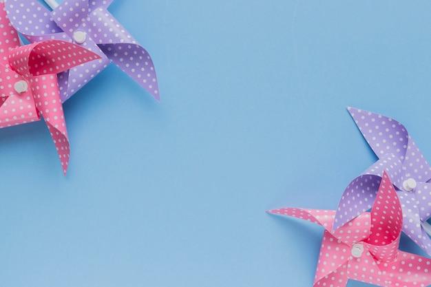 O cata-vento pontilhado cor-de-rosa e roxo da polca arranja no canto do contexto azul