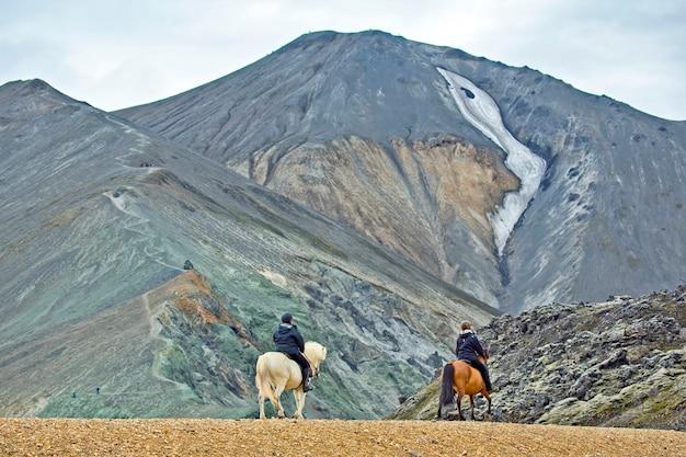 O cavaleiro cavalga em um cavalo islandês em uma paisagem montanhosa