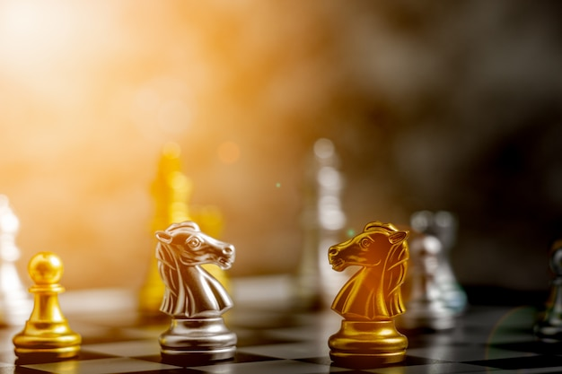 O cavaleiro de ouro em pé encontra um cavaleiro de prata no xadrez.