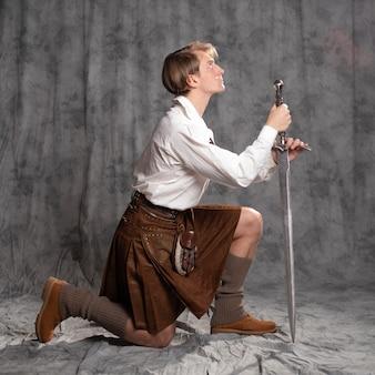O cavaleiro escocês ajoelhou-se e fez um juramento conceitual de um jovem com um kilt