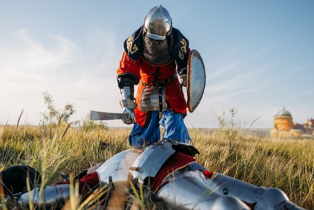 O cavaleiro medieval com armadura e capacetes colocou sua espada na garganta de seu oponente. antigo guerreiro com armadura posando no campo