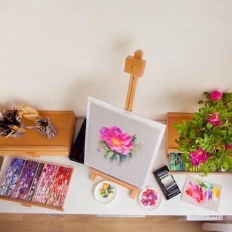 O cavalete de madeira de uma flor de rosa mosqueta está sobre uma mesa ao lado dos materiais para desenhar com pincéis, lápis e pastel seco. conceito de local de trabalho de uma artista feminina. copyspace