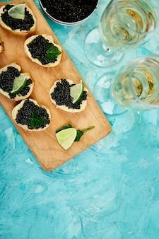 O caviar preto do esturjão na bacia, em sanduíches e no champanhe de madeira no fundo branco copia o espaço.