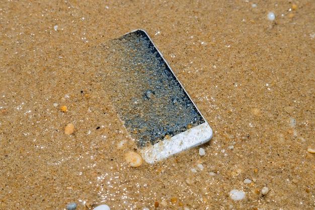 O celular perdido cai na água do mar perto da praia.