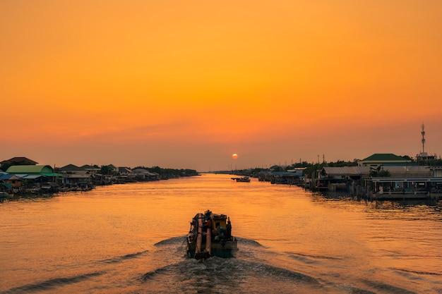O cenário da comunidade de pescadores em que um barco de pesca está navegando no canal para sair para o mar e encontrar peixes à noite