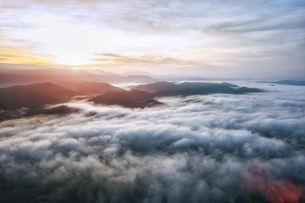 O cenário no cume, silhueta da montanha acima das nuvens no nascer do sol.