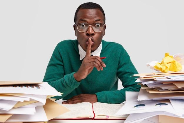 O ceo afro-americano secreto mostra sinal de silêncio, trabalha na tarefa recebida do chefe, anota ideias no caderno, tem expressão facial surpresa