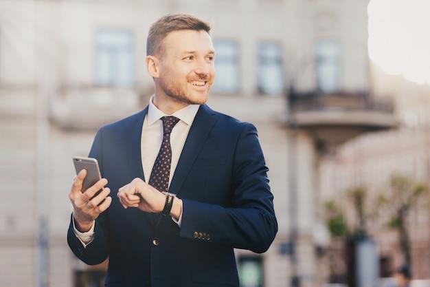 O ceo masculino com barba bem-sucedido procura arquivos de multimídia interessantes no telefone inteligente